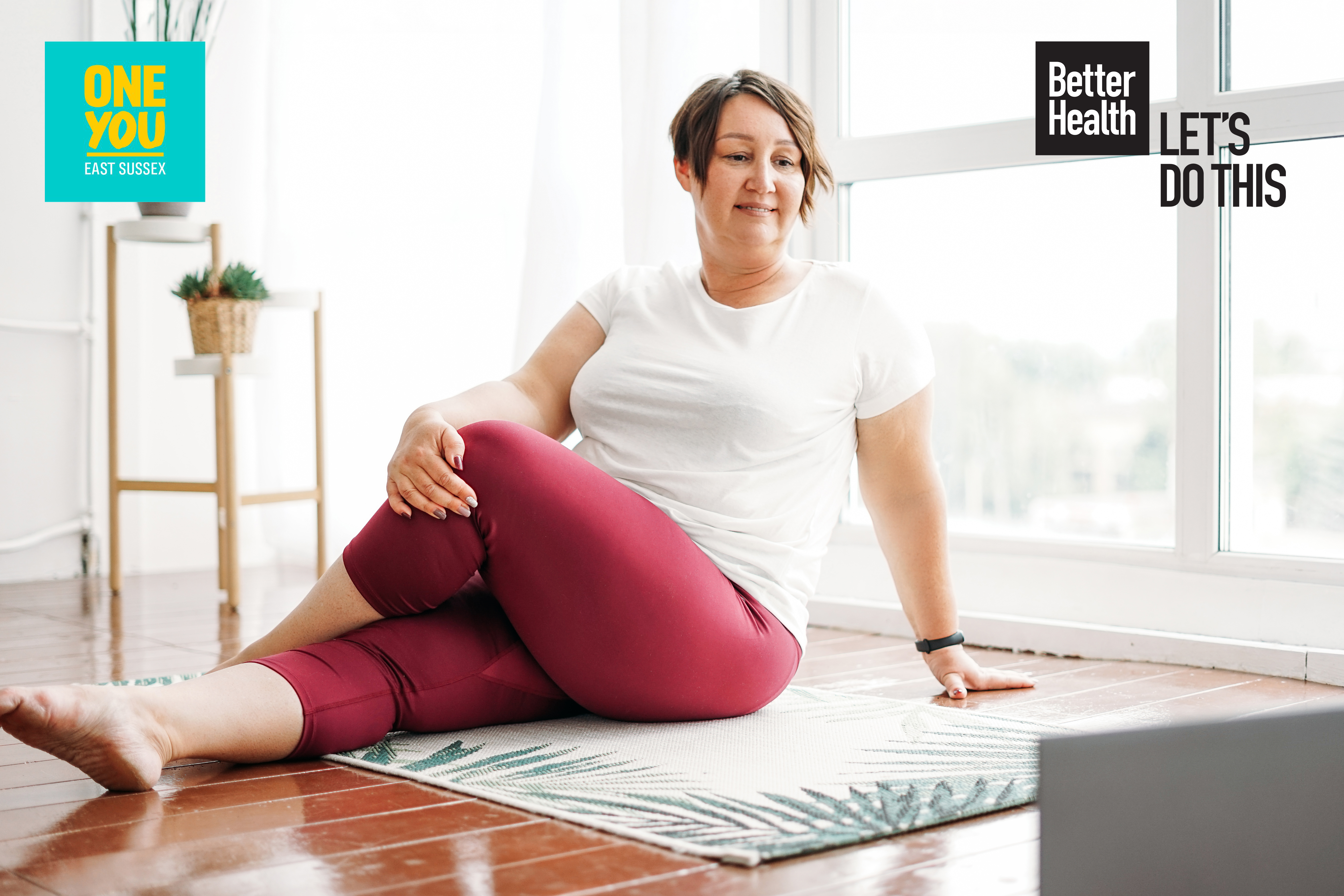 Woman doing leg stretching exercises on a mat on the floor